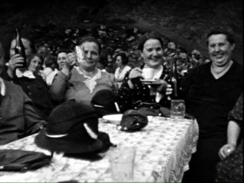 stockvideo's en b-roll-footage met 1938 b/w montage women drinking beer, toasting and singing outdoors / thuringia, germany  - 1938