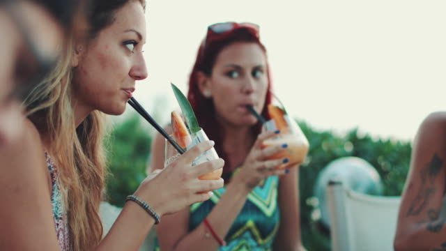 Women drinking fruit cocktail during aperitif by the sea