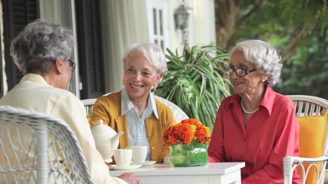 ms pan women drinking tea and talking on house porch, granddaughter (8-9) giving birthday present / richmond, virginia, usa - großmutter stock-videos und b-roll-filmmaterial