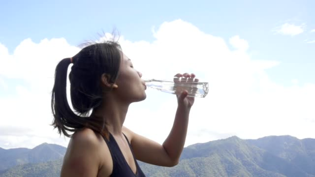women drinking water after run, slow motion