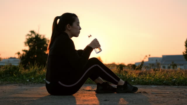 women drinking water after running in sunset time - relaxation exercise stock videos & royalty-free footage