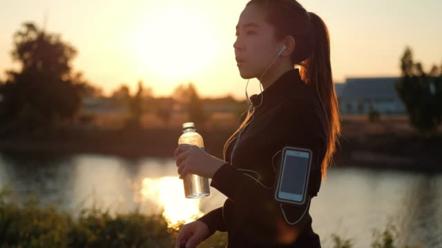 women drinking water after running in sunset time - early morning exercise stock videos & royalty-free footage