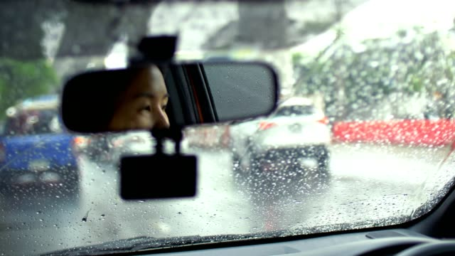 4k : women driving car in the rain - tail light stock videos & royalty-free footage