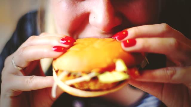 魚ブルジェを食べる女性 - unhealthy eating点の映像素材/bロール