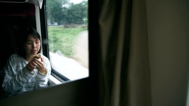vidéos et rushes de femmes manger cupcake dans le train - tourist