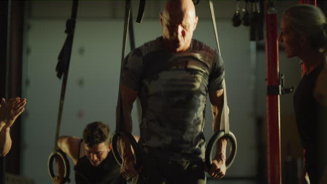 stockvideo's en b-roll-footage met women encouraging man doing push-ups on gymnastic rings / lehi, utah, united states - lehi
