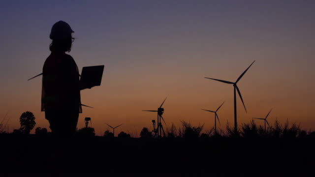 women engineer using laptop with wind energy turbine at sunset - exhaustion stock videos & royalty-free footage
