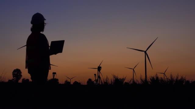vídeos de stock, filmes e b-roll de coordenador das mulheres que usa o portátil com a turbina da energia eólica no por do sol - turbina