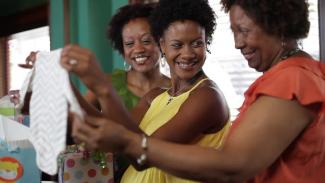 women enjoy opening gifts at a baby shower. - baby shower stock videos and b-roll footage