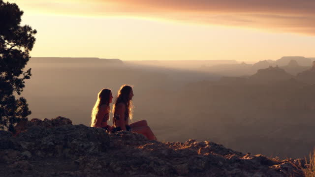 Women enjoying sunset view and offering help to other as she stands