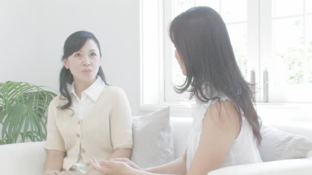 women enjoying talking on couch - 2人点の映像素材/bロール