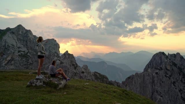 stockvideo's en b-roll-footage met ws vrouwen genieten van rustige uitzicht op de bergen bij zonsondergang, julian alps, mangart, slovenië - julian alps
