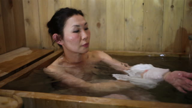 women enjoys indoor cedar wood ofuro near minakami, gunma, japan - 裸点の映像素材/bロール