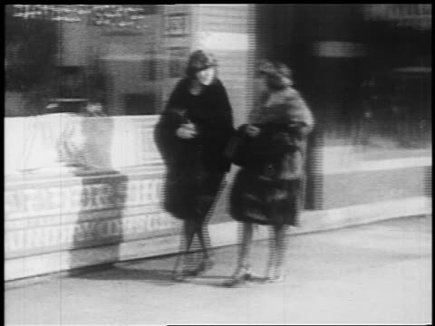 b/w 1925 pan 2 women entering barber shop / newsreel - barber stock videos & royalty-free footage