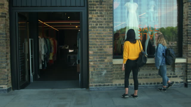 stockvideo's en b-roll-footage met women entering boutique - etalage