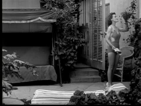 vídeos de stock e filmes b-roll de 1937 b/w ws women entering patio, taking off top, and lying down to sunbathe - despir