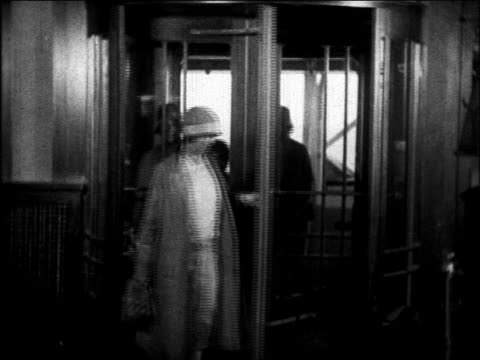 b/w 1930 women entering room from deck of ocean liner thru revolving door / educational - revolving door stock videos & royalty-free footage