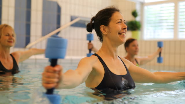 women exercising with dumbbells in swimming pool - physical therapy stock videos & royalty-free footage