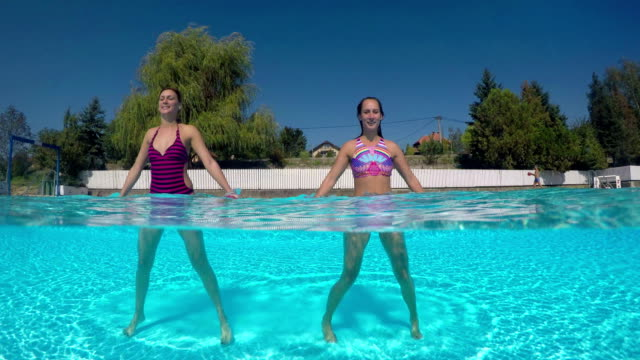 women exercising with dumbbells in swimming pool - step aerobics stock videos and b-roll footage