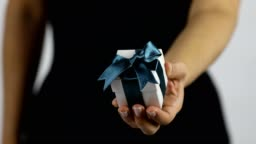 A women extends a gift in a white box with dark blue ribbon towards the camera