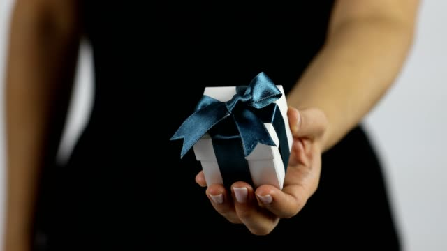 a women extends a gift in a white box with dark blue ribbon towards the camera - tied bow stock videos & royalty-free footage