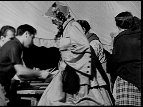 vídeos y material grabado en eventos de stock de women extras in native american & western costume clothing being handed vouchers. samuel goldwin studios building on lot. vs actors in costume... - 1930 1939