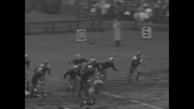 QS women fans in hooded raincoats / Notre Dame Fighting Irish kickoff to Army Black Knights on rainy field at Yankee Stadium / Army's Woodrow 'Woody'...