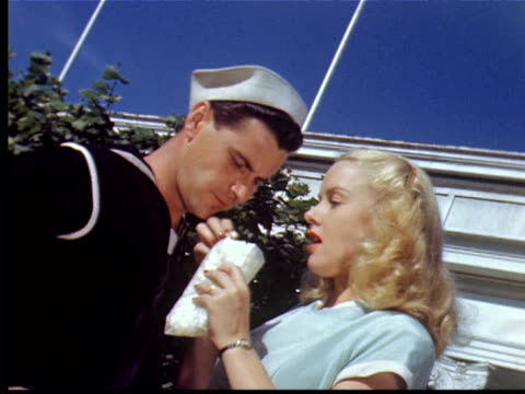 1943 ms women feeds popcorn to sailor boyfriend while he tries to kiss her. they laugh + point at camera / coney island, new york city, usa - 1943 stock videos and b-roll footage