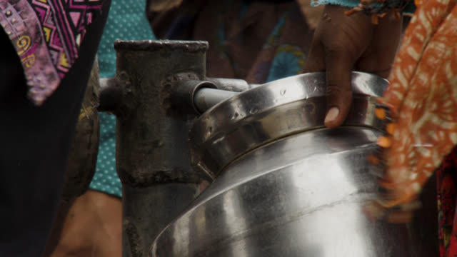 women fill water containers from pump, india. - community stock videos & royalty-free footage
