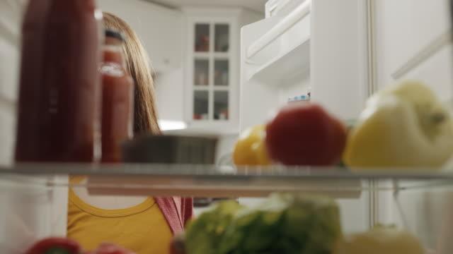 stockvideo's en b-roll-footage met vrouwen die ijskast met kruidenierswaren vullen - gevuld