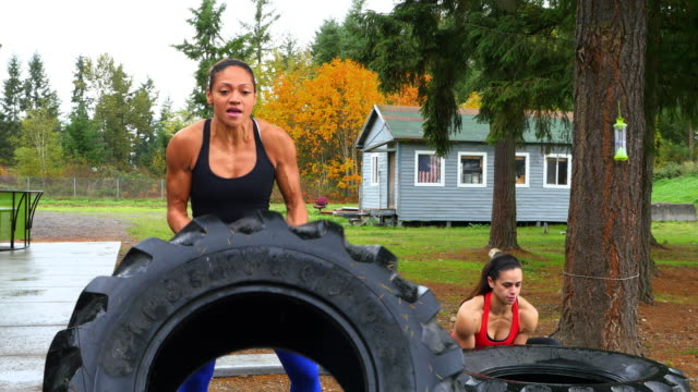 vídeos de stock, filmes e b-roll de ms ts women flipping tractor tires outside during gym workout - treino cruzado