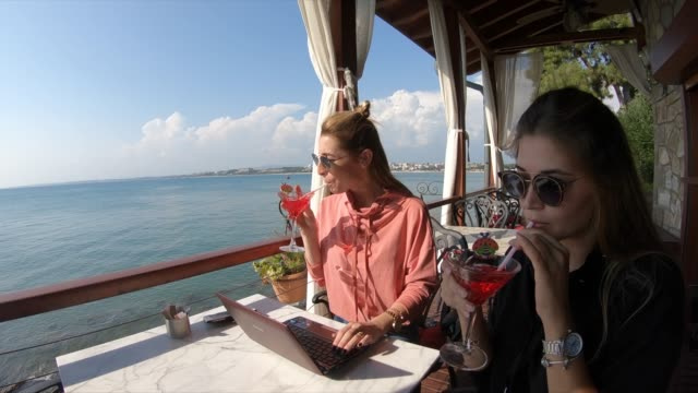 women friends at outdoor cafe  working on laptop - holiday villa stock videos & royalty-free footage