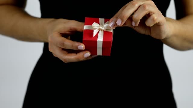 a women gets a present in a red giftbox with white ribbon and starts to untie the ribbon - ribbon bow stock videos & royalty-free footage