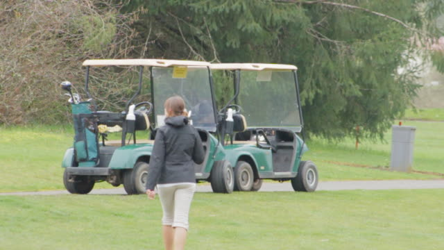 women gets in a golf cart and drives to the next hole - golf cart stock videos and b-roll footage