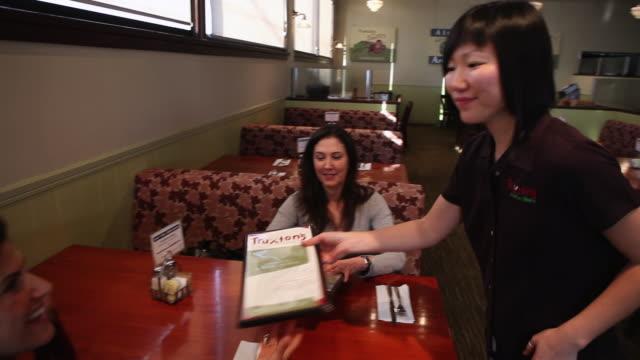 stockvideo's en b-roll-footage met ms pan women giving menus to customers  / truxton's, california, usa - tafelmanieren