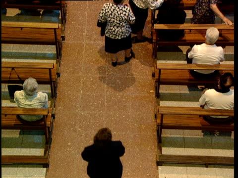 stockvideo's en b-roll-footage met women go to sit down on pews in catholic church basque country spain - gelovige