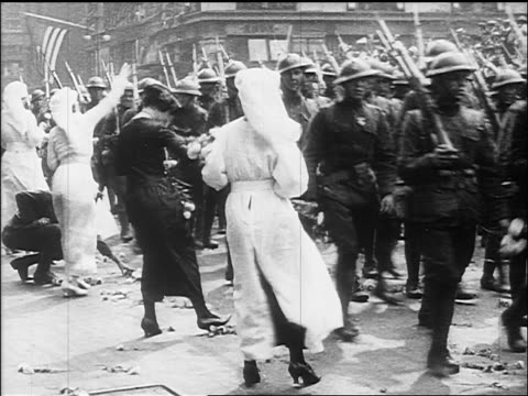 vidéos et rushes de b/w 1918 women hand flowers to soldiers marching in victory parade / end of ww - 1918