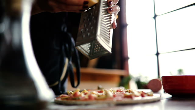 women hand grating the cheese on the pizza - grater utensil stock videos and b-roll footage