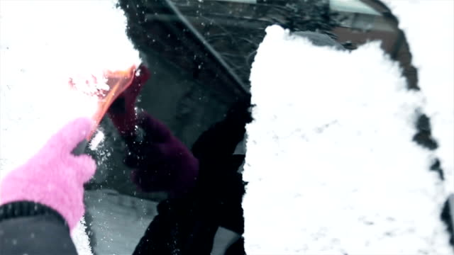 women hand in pink  glove removes snow from car windshield in winter day - scraping stock videos and b-roll footage