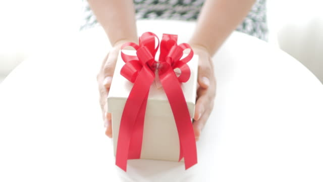 Women hands put down a gift box on white table background
