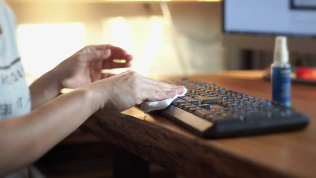 cu of women hands using alcohol spray and wiping down surfaces on a computer keyboard for cleaning and protect covid-19 - dustman stock videos & royalty-free footage