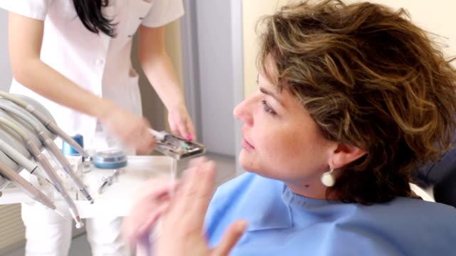 stockvideo's en b-roll-footage met vrouwen net klaar is met tandheelkundige afspraak, handheld schot - tandarts