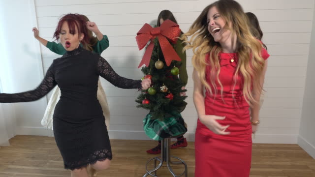 women having fun as they dance around a small christmas tree - weihnachtsbaum stock-videos und b-roll-filmmaterial