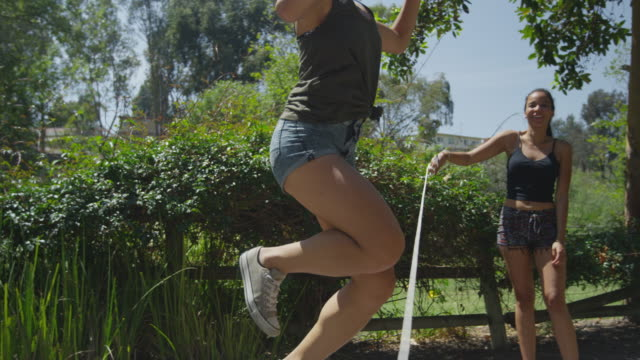 women having fun at the park jumping rope - skipping along stock videos & royalty-free footage