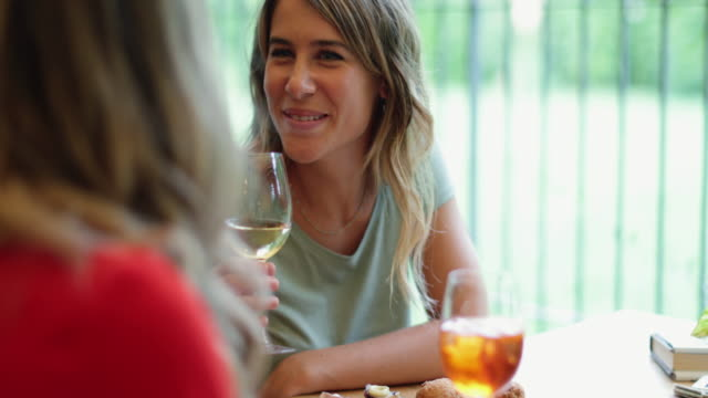 women having italian aperitivo together, drinking wine with social distancing - aperitivo video stock e b–roll