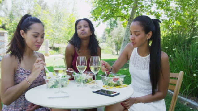 women having lunch outdoors together - durevolezza video stock e b–roll