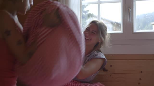 Women having pillow fight in chalet