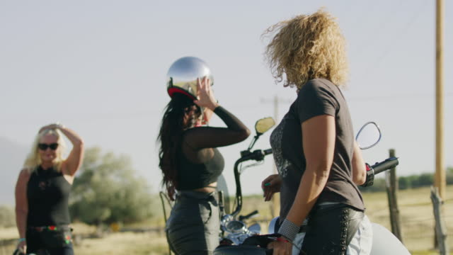 vidéos et rushes de women high-fiving and hugging after riding motorcycles / payson, utah, united states - payson