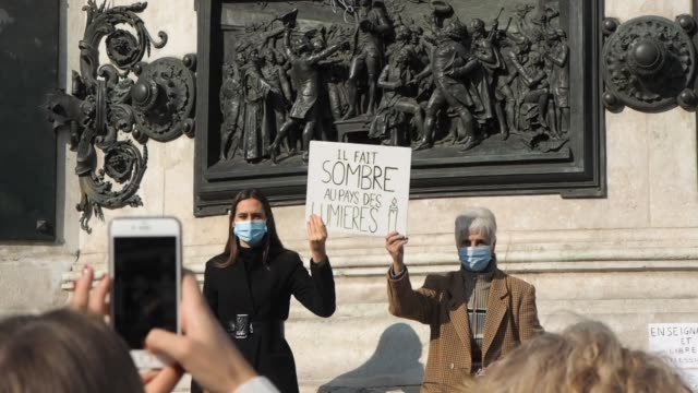 women hold signs in front of the monument as people gather in place de la république to pay tribute to professor samuel paty and to defend freedom of... - decapitated stock videos & royalty-free footage