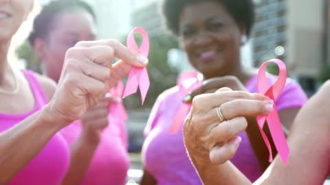 vídeos de stock e filmes b-roll de women holding breast cancer awareness ribbons - volunteer